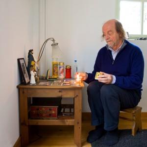 Foto van de taalvirtuoos Guido de Wijs bij zijn huisaltaar.